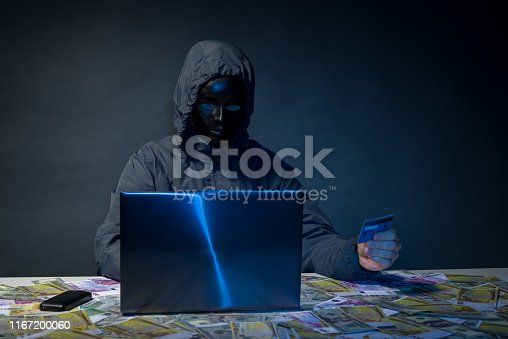 istock Anonymous hacker in mask programmer uses a laptop to hack the system in the dark. 1167200060