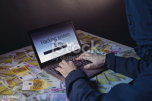 istock Anonymous hacker programmer uses a laptop to hack the system in the dark. Creation and infection of malicious virus. The concept of cybercrime and hacking database 1170085027