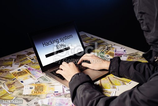 istock Anonymous hacker programmer uses a laptop to hack the system in the dark. Creation and infection of malicious virus. The concept of cybercrime and hacking database 1178753344