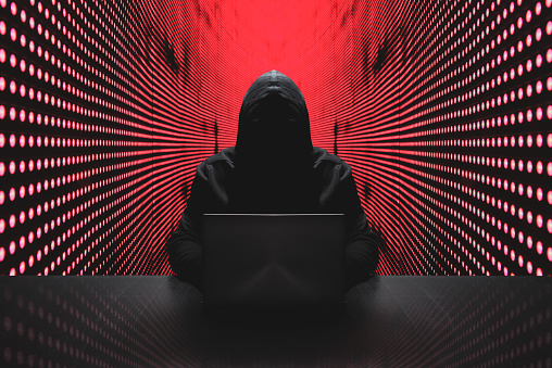 Anonymous hacker in front of his computer with red light wall backgroundAnonymous hacker in a black hoody with laptop in front of a code background with binary streams cyber security concept