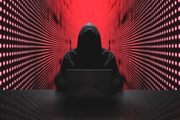 Anonymous hacker with laptop in front of binary code cyber security Anonymous hacker in front of his computer with red light wall backgroundAnonymous hacker in a black hoody with laptop in front of a code background with binary streams cyber security concept computer crime stock pictures, royalty-free photos & images
