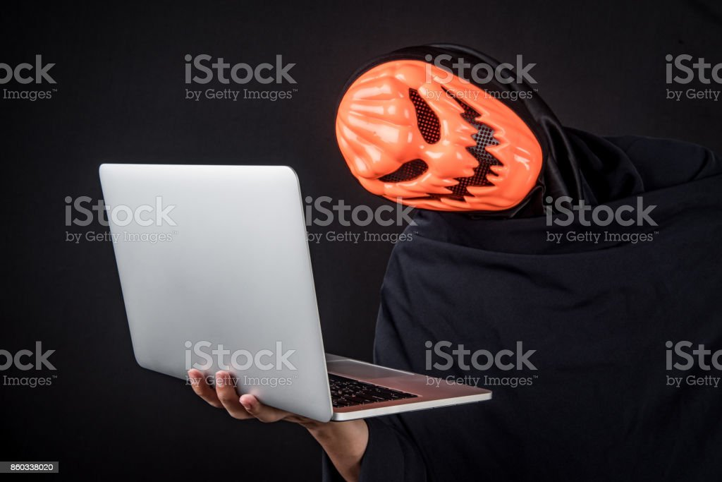 Anonymous male hacker with pumpkin halloween mask carrying laptop computer stock photo