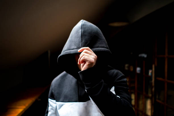 anonymous man in the dark hood standing in the mysterious pose f anonymous man in the dark hood standing in the mysterious pose creepy stalker stock pictures, royalty-free photos & images