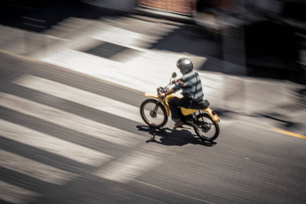Anonymous man riding motorbike on street stock photo