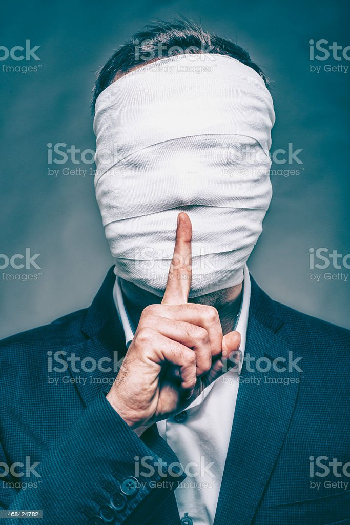 Anonymous man with face hidden makes sign to be silent stock photo