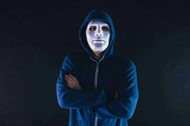 Anonymous masked man under hoodie with arms crossed isolated over dark background - incognito and mysterious criminal on internet activities concept. Anonymous masked man under hoodie with arms crossed isolated over dark background - incognito and mysterious criminal on internet activities concept creepy stalker stock pictures, royalty-free photos & images