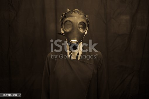 Unrecognizable young woman in scary gas mask looking at camera while standing on dark background