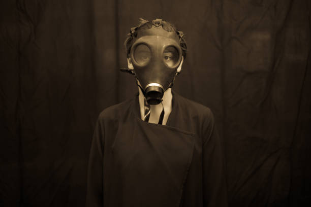 Anonymous model in gas mask Unrecognizable young woman in scary gas mask looking at camera while standing on dark background radioactive contamination stock pictures, royalty-free photos & images