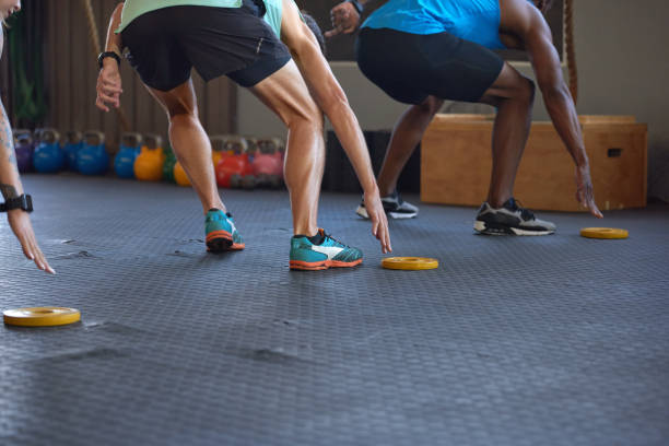 Anonymous people lunging in the gym during a fitness sprint stock photo