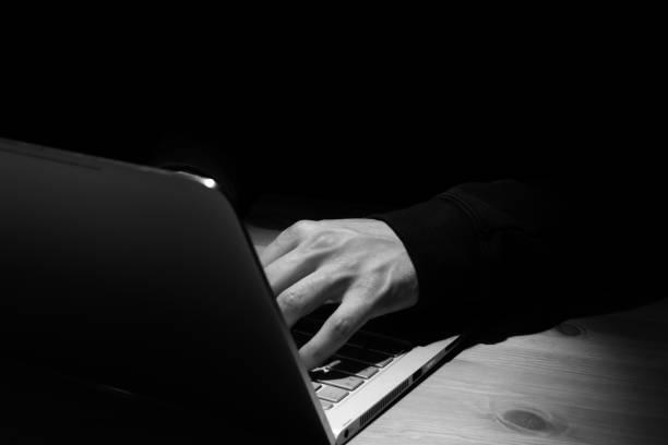 Anonyme Person mit Notebook im Dunkeln. – Foto