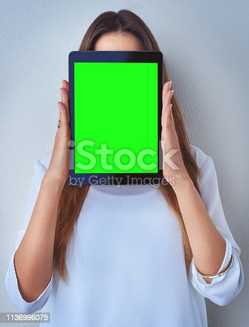 Shot of an unrecognizable woman holding a digital tablet against a blue background