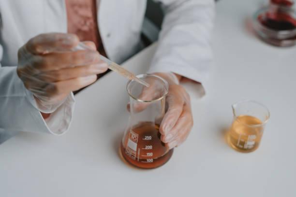 anonym forskare / kemist i en vit lab coat med hjälp av en dropper att lägga till något till en erlenmeyer kolv på ett labb - laboratory add flask bildbanksfoton och bilder