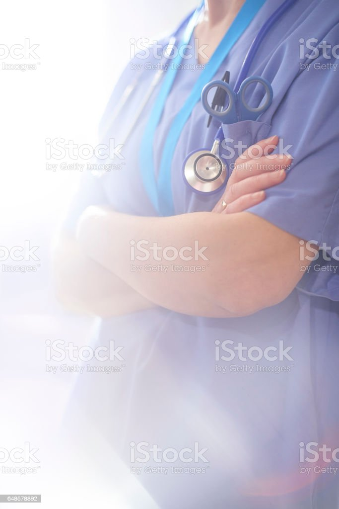 Anonymous surgeon stood with arms folded stock photo