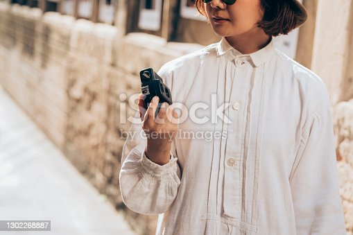 An unrecognizable Asian woman standing in the street with a camera in her hand.
