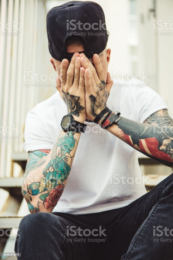 Anonymous trendy man covering face stock photo