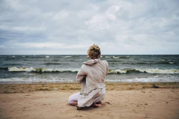 Anonymous woman in jacket looking at sea stock photo
