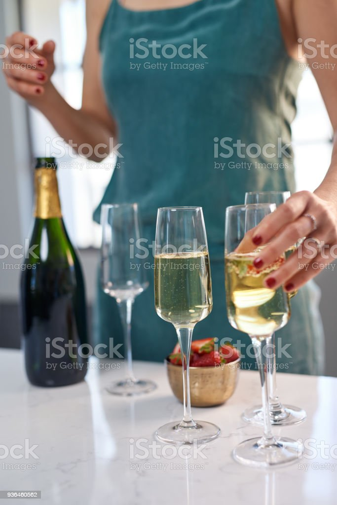 Anonymous woman laying out glasses of sparkling wine for guests stock photo