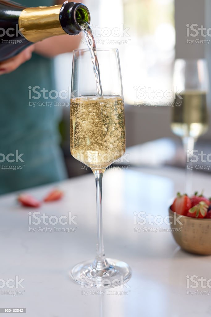 Anonymous woman pouring a glass of sparkling wine into tall glass stock photo