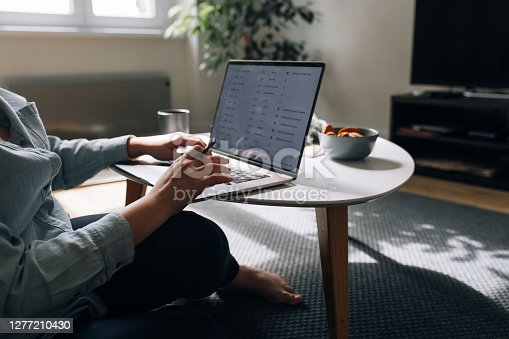 Hands of an unrecognizable woman sitting on the floor and using her computer to work, adapting to the new normal concept.