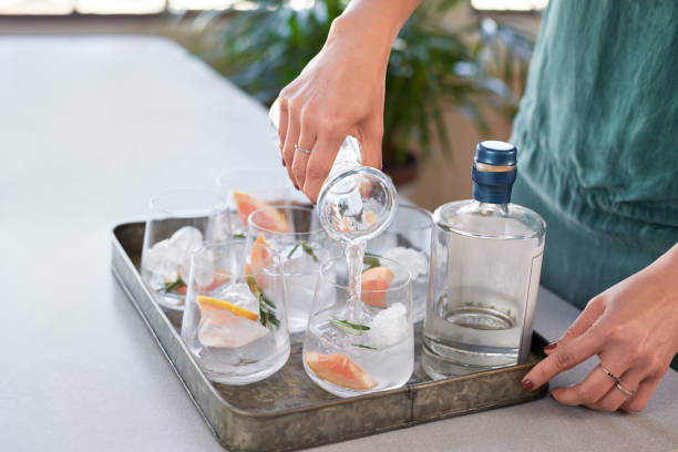 Anonymous woman's hands pouring drinks into glasses in a drinks tray Woman pouring tonic soda water into glasses, preparing alcoholic beverages at a party vodka stock pictures, royalty-free photos & images
