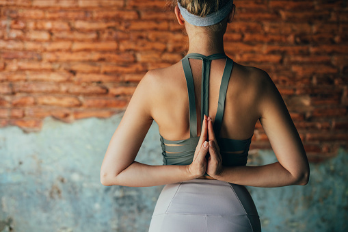 Back view of an unrecognizable woman in sports clothes exercising at home