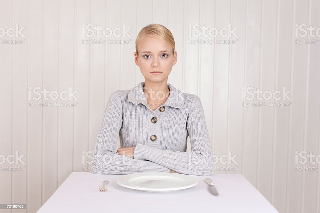 Anorectic woman in front of empty plate stock photo