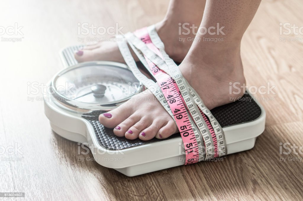 Anorexia and eating disorder concept. Feet tied up with measuring tape to a weight scale. Addiction and obsession to weight loss. stock photo