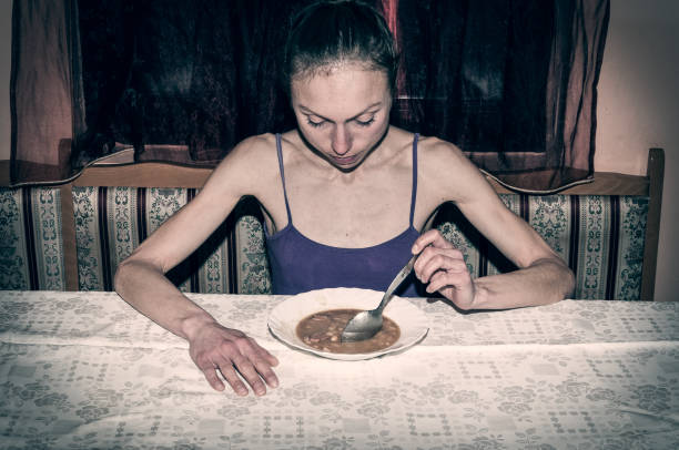 Anorexia. Skinny anorexic girl holding a spoon and look at the plate with food. stock photo