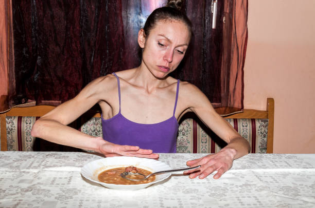Anorexia. Young skinny woman with anorexia refusing to eat. stock photo