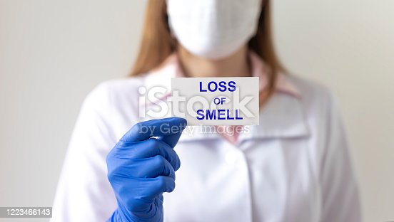 Anosmia loss of sense of smell. Loss of smell text on white paper in hands in protective gloves with blurring doctor on background