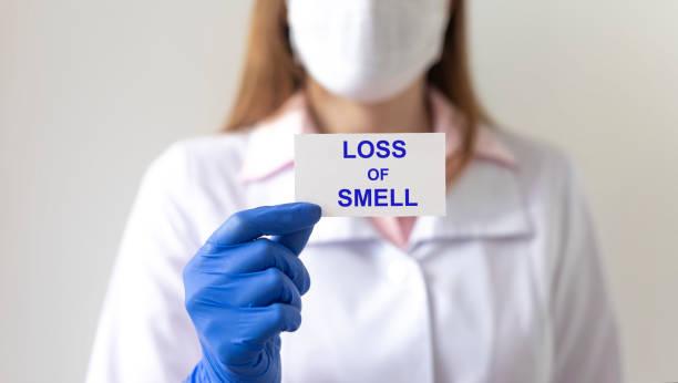 후각의 무혈증 손실. 백서에 백서에 냄새 텍스트의 손실 은 배경에 흐리게 의사와 보호 장갑에 손에 - 향기로운 뉴스 사진 이미지
