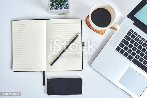 High angle shot of a laptop, notebook and smartphone on a work desk