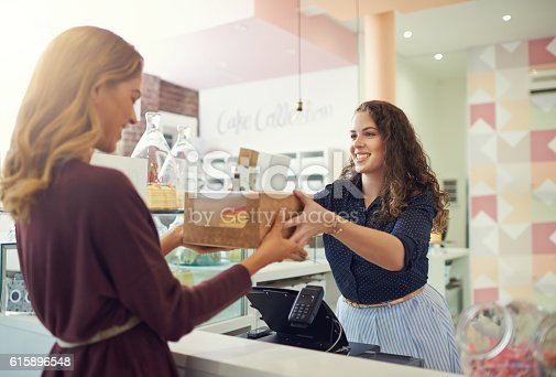 Shot of a young woman handing a box to a customer in her cake shop