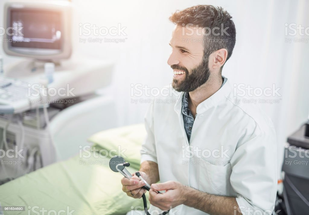 Another day at work for happy male mid adult doctor. stock photo