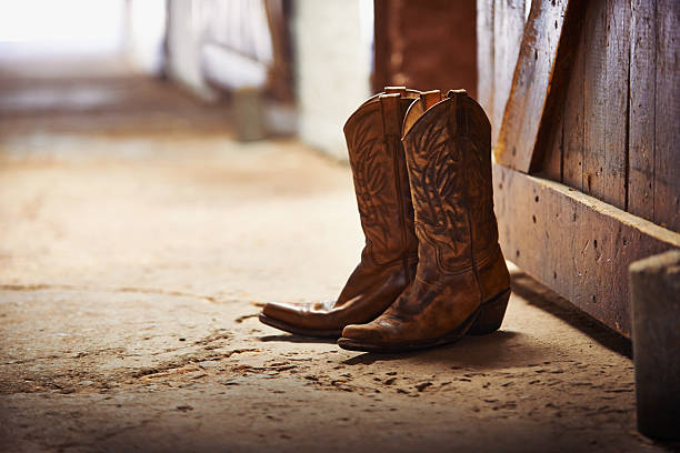 Another day done Shot of a pair of cowboy boots in a barn ranch stock pictures, royalty-free photos & images
