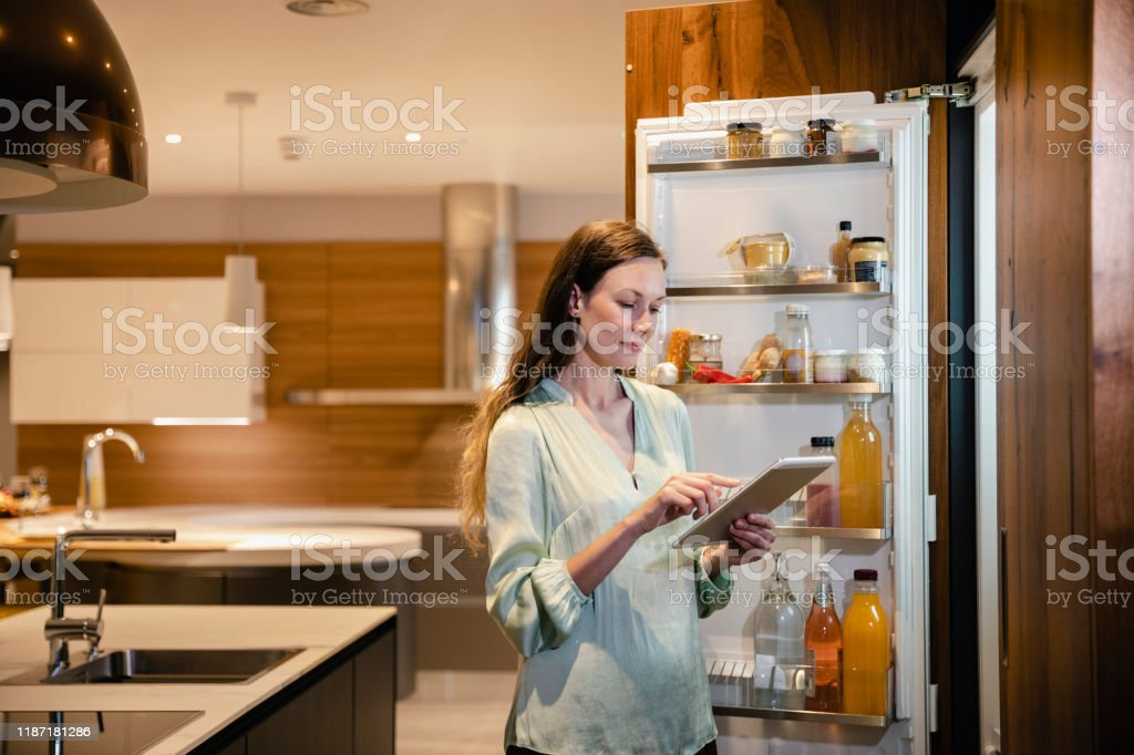 Another Item in the Shopping List A side-view shot of a caucasian woman looking into her smart fridge and adding groceries to her shopping list using a digital tablet. 30-39 Years Stock Photo