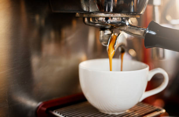 Another one thank you Closeup shot of an espresso maker pouring coffee into a cup inside of a cafe caffeine stock pictures, royalty-free photos & images