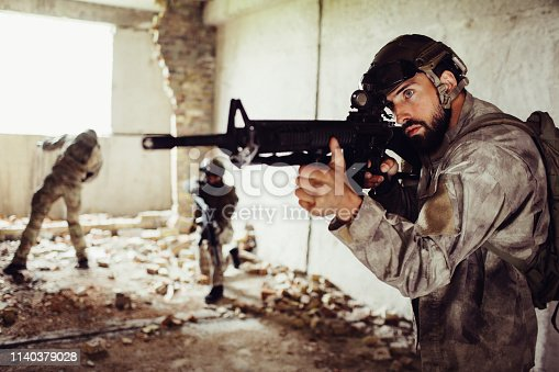 istock Another picture of brave soldiers. Bearded man is standing in front with rifle. Second guy is standing in the middle of room on one knee and looking straight. Third one is near window. 1140379028