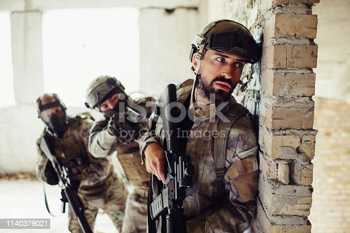 istock Another picture of man in uniform standing behind wall and waiting. There are tow guardians behind bearded man. They are covering him. Man in front is holding his rifle down. 1140379021