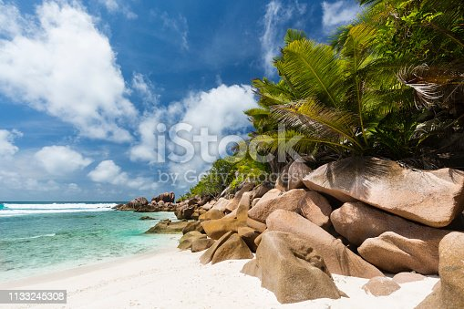 Perfect white beach Anse Cocos in La Digue, Seychelles with granite boulders and palm trees