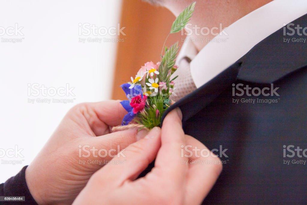 Ansteckblume wird dem Braeutigam angesteckt – Foto