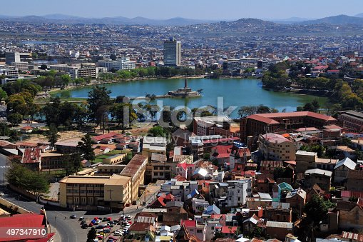 Antananarivo, Madagascar: skyline - view from the Haute Ville - Anosy Lake with its War Memorial at the end of a causeway - panoramic view of downtown - photo by M.Torres