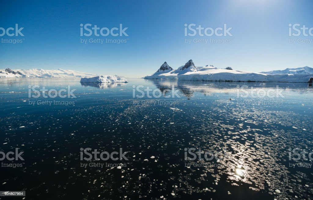 Antarctic Landscape with Sun Reflected in Pancake Ice stock photo
