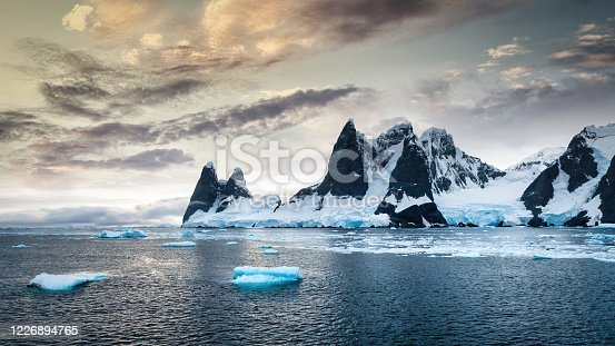 Antarctica Peninsula Glacier Mountain Range Panorama under moody colorful early morning twilight. Icebergs and Icesheet floating on the calm Antarctic Ocean. Antarctica Peninsula, Antarctica