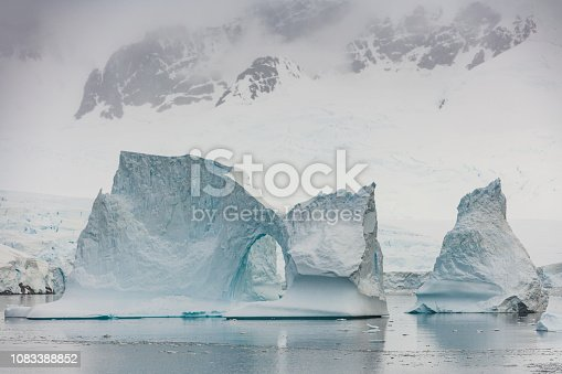 Antarctica Neumeyer Channel Iceberg with Natural Ice Arch in front of Antartica Peninsula Glaciers drifting on the Antarctic Ocean. Neumeyer Channel, Antarctic Ocean, Antarctica.