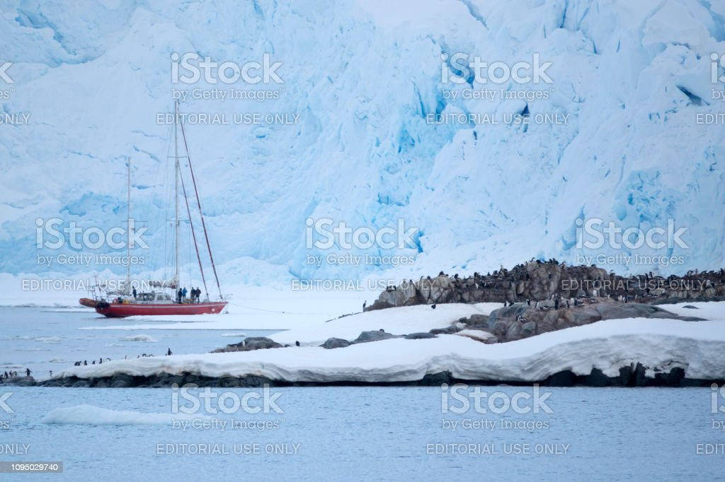 Antarctica sailboat explorers gentoo penguins Wiencke Island mountain glaciers Port Lockroy station stock photo