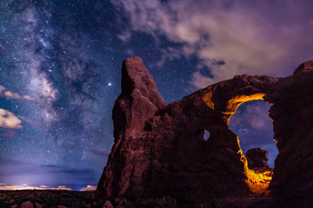 Antares and Milky Way over Turret Arch Two light sources on Turret Arch: one manmade, one mother nature, Lightning, light up Turret Arch in Arches National Park, Utah. arches national park stock pictures, royalty-free photos & images