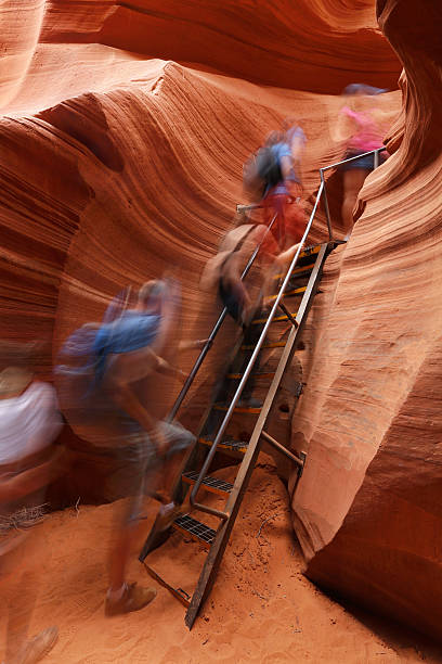 antelope canyon with people climbing ladder - lower antelope canyon stock photos and pictures