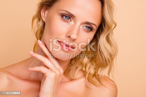 Anti age wrinkle facial care advertising concept. Close-up cropped portrait of attractive wavy-haired lady with smooth flawless pure fresh healthy clean clear skin isolated on beige pastel background.