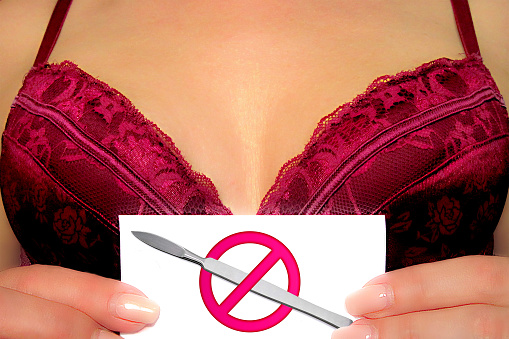 istock Anti breast augmentation concept image. Girl holds card with scalpel and prohibition sign in front of bust in bra or decollate dress. Plastic surgery procedure negative decision for woman health 1155392605